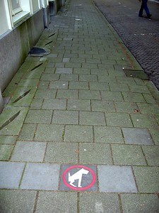 This sign, on the sidewalk outside the Danish Embassy, apparently requests that dogs be placed there