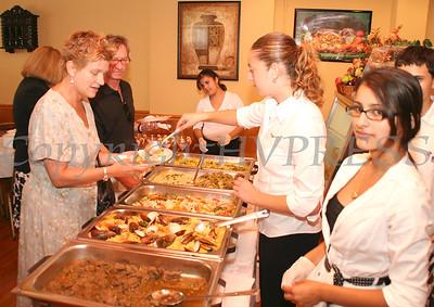 Jean Ann McGrane and Chuck Thomas are served Peruvian food by Christina Figueroa and Sharon Conejo