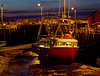 Dusk and low tide. A commercial fishing trawler sits on the bottom of the harbour.<br /> 20:55 R