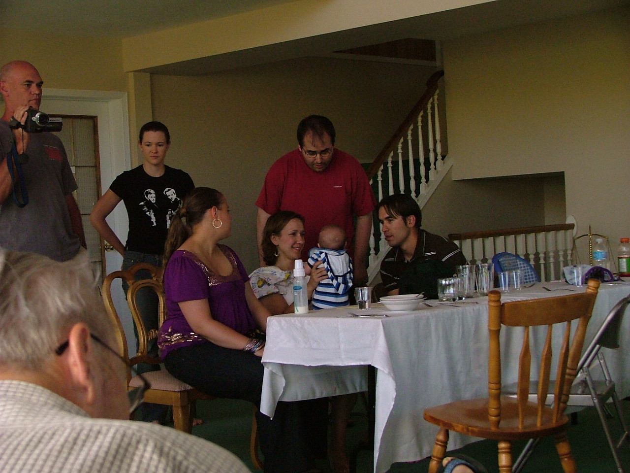 Kelly (camcorder), Amanda (black shirt), Paul (red), Jordan (purple), Erica (with baby Liam), and Scott (brown stripes)