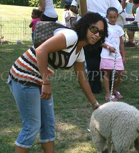 Amanda Bashante pets a sheep while Daraya Davis holds the rope