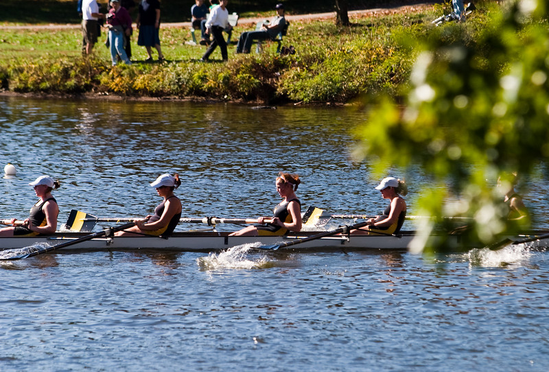 A shell passes spectators on the bank of the Charles.