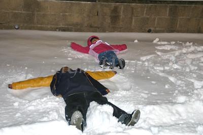 children make snow angeles outside the rec center