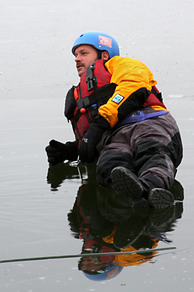 Water Rescue Chief Cliff Silvers floats gently on a sheet of ice, supervising the operations.