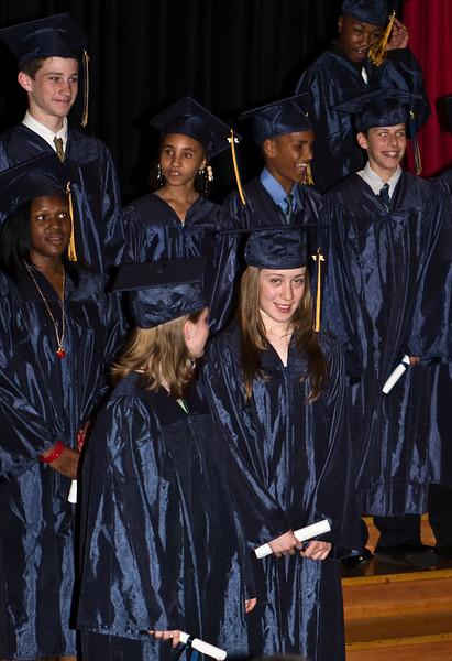 Graduates smiling with diplomas.