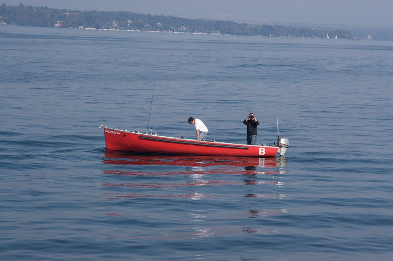 Fishing • A couple of men out on Lake Geneva for some Saturday-morning fishing. One of the men seems more intent on closely examining our tour-boat with his binoculars.
