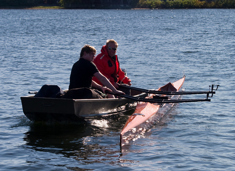 Wet rower returns with his capsized boat.