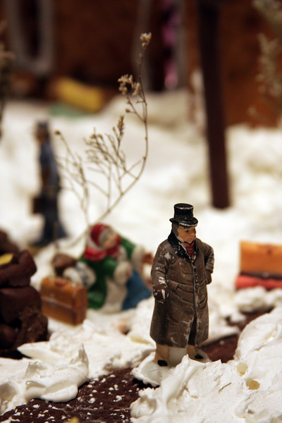 A small plastic man stands amid frosting snow in the gingerbread city at the Captain Cook Hotel.