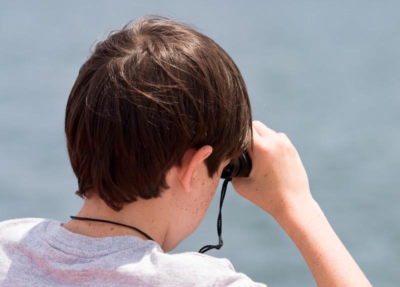 Benjamin peering through binoculars.