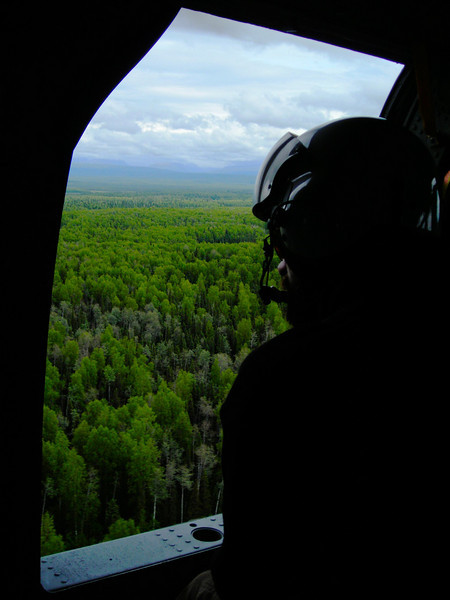 A firefighter watches fascinated from the window of the blackhawk on the flight back to the road system.