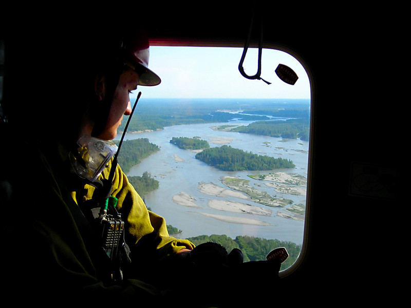 The Susitna River passes underneath as Adam Webber sits glued to the window.