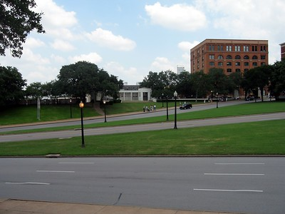 View across Dealey Plaza, with the Grassy Knoll on the left and the former Texas School Book Depository on the right.  The car in the center of the photo is on almost the exact spot on which the fatal shot hit President Kennedy.