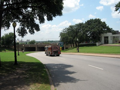 A fire truck passes a few yards in front of the spot on which the fatal shot hit President Kennedy.