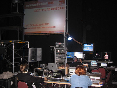 Backstage during the election of officers.  The back of the screen above the main podium is at the top of the photo.  The table in the foreground includes the teleprompter operator on the left and the timer operator on the right.  The table in the background includes the video switching equipment and operator on the left and the audio and slideshow laptops on the right.  The monitors on the upper right show the two camera feeds.