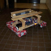 The drivetrain of the robot with its finished bumppers, and a wooden structure built to temporarily hold the electronics board, and put weight on the center of gravity determined from our design 1/25/09.