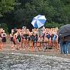 The first heat of swimmers getting ready to run into the lake.