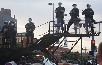 Police on elevated platform, in riot gear, armed with tear gas guns.