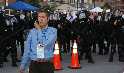 News media photographer, talking on cell phone,looking apprehensive, standing in front of a formation of police in riot gear, at the Democratic Convention in Denver.