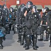 Police outfitted in riot gear, standing in formation while on duty at the 2008 Democratic National Convention in Denver.