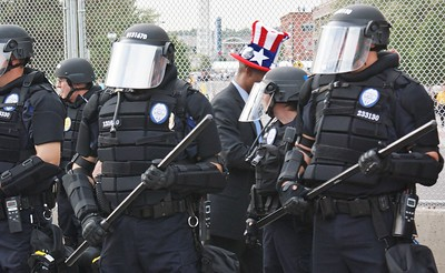 "Police in riot gear with battons, behind them a man in large ""Uncle Sam"" hat passes by."