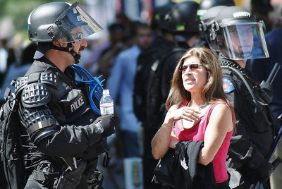 Police officer in riot gear at 2008 Democratic National Convention in Denver, chatting with a woman on the downtown mall.