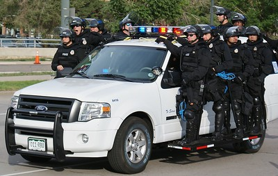 Police in riot gear, riding on the running boards of a police SUV, on duty at the 2008 Democratic Convention in Denver. One officer yawning.