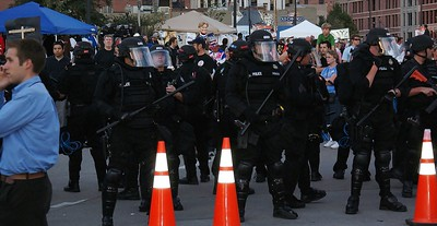 line of police in riot gear, in background large number of spectators.