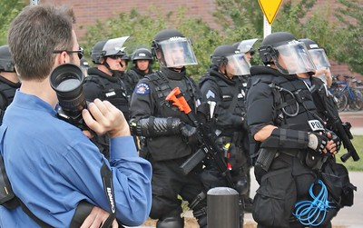 Police officer in riot gear and carrying an automatic weapon, while on duty at the 2008 Democratic Convention in Denver, in front of them man holding camera.