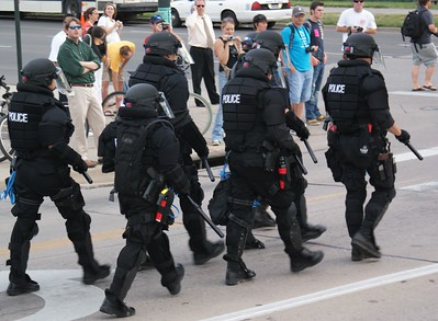 Bystanders outside the 2008 DNC in Denver watch police in riot gear walk by.