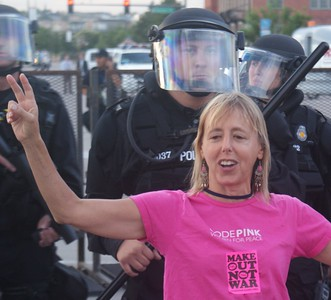 """Code Pink"" member Medea Benjamin flashes the peace sign in fron of police in riot gear at the 2008 DNC in Denver."