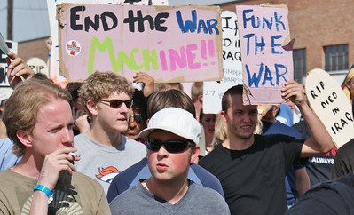 Group of young men carry anti-war signs during march at 2008 DNC in Denver.