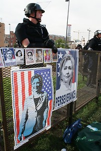 Police officer in riot gear standing behind a fence with Hillary Clinton posters on it.