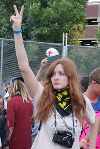 "Young woman raises hand in ""peace sign"" during march against the Iraq war at the 2008 DNC in Denver."