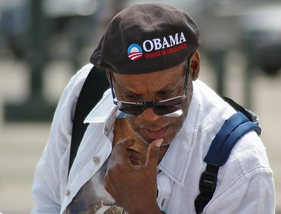 Man wearing Obama hat looks at merchandise for sale at the 2008 DNC in Denver.