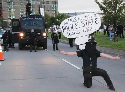 Protester at the 2008 Democratic Convention, commenting on police in riot gear and armored police vehicle.