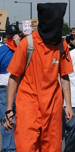 Man wearing orange jumpsuit and hood over his head as protest against conditions at Quantanimo, marches against the Iraq war at the 2008 DNC in Denver.