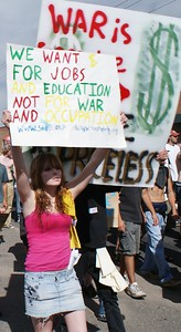 Protesters with signs and banners march against the Iraq war at the 2008 DNC in Denver.