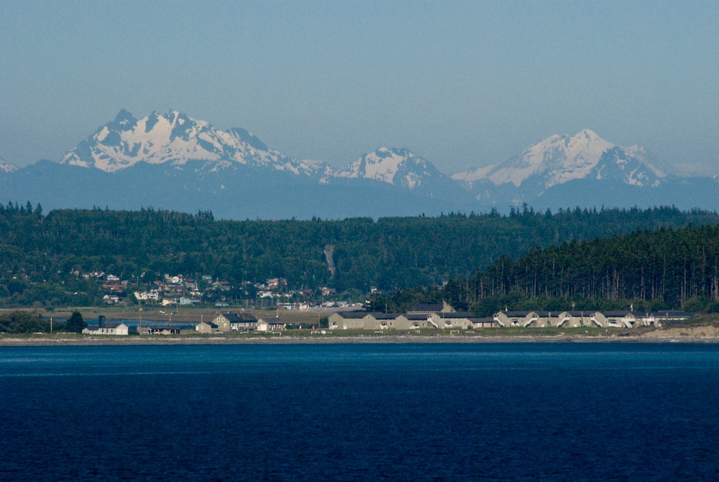 Cascade mountains over Whidbey island.  I think this is the air force base in the foreground?