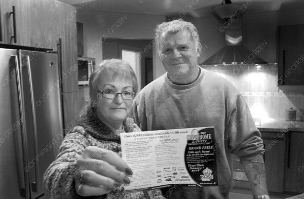 Citizen photo by Chuck Nisbett Linda Naef and husband Stan Rogalski display the winning ticket while standing in the kitchen of their new home at 2515 McTavish Drive courtesy of the Spruce Kings Home Lottery Tuesday afternoon.
