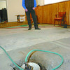 Citizen photo by Brent Braaten Pat Martin stands between three sump pumps in the basement of his home in Del Haven Tuesday morning. Martin has five pumps pumping the water out of his basement. He has had to rip up the carpet and jack hammer holes and trenches in his basement floor to manage the water.