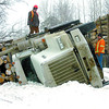 Citizen photo by David Mah A loaded logging truck drives by an overturned truck at Chief Lake Road and Lakeshore Drive by Ness Lake. The logging truck heading to Prince George chose the ditch to miss an oncoming pickup.