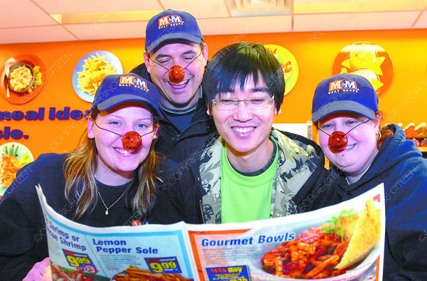 Citizen photo by David Mah Kristen Traxler, left, with M&M Meat Shop, owner Paul Waterfield and Lucia Bonin look over customer Ron Huang's shoulder as he looks at a flyer Friday which was M&M's 17th annual Red Nose Day. Red Nose Day lightens and brightens the long days of winter.
