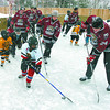 Citizen photo by David Mah Michael Van Unen, 9, keeps the puck away from Patrik Magnusson, right, and Greg Gardner at the Raju home on Marleau Road. The family won the 'Local Neighborhood to Take on Cougars' Home Depot Backyard Rinks Contest. There were about 30 children taking part.