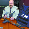 Citizen photo by David Mah Const. Gary Godwin shows weapons and bullet proof vest seized at a roadblock on Friday.