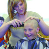 Citizen photo by David Mah Cedars Christian School student Melissa Gordon, 11, has her head shaved by Lisa Reimer from Loxx Academy at the fundraiser for grade 5 student Sam Goertzen. Sam has Acute Lymphoblastic Leukemia. At haircut time $9795.16 had been raised for the family. The target was $4,000.00