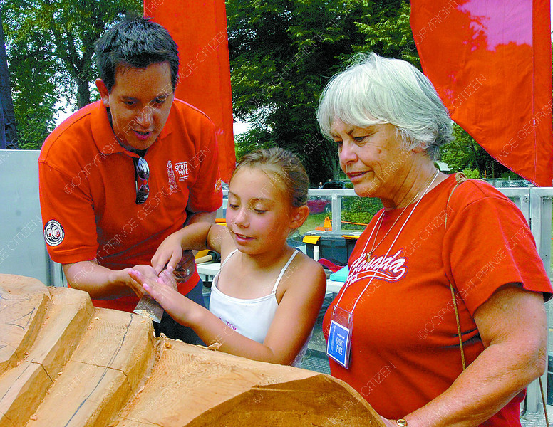 Citizen photo by David Mah Master Carver Carey Newman, left, helps Lexi Ballum, 9, and her grandmother Shirley Ballum carve a bit of the Spirit Pole at Canada Day at Fort George Park.