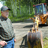 Citizen photo by Brent Braaten Harold Rimmer stands next to his back-hoe that is blocking Cranbrook Hill Road. He is involved in a disagrement with the City of Prince George over the road going through his property.