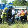 Citizen photo by Brent Braaten City of Prince George Fire Rescue Department and BC Ambulance Paramedics help the driver of a truck that turned over on its side off of a burm at Citizen Field near Massey Drive.