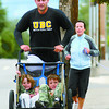 Citizen photo by Chuck Nisbett Family Fitness - Justin Frey is followed by wife Cathy, leading the family dog Kaya (out of the picture), as he pushes Carson, 3 (left), Neala, 10-months-old, and Avery, 5, on their morning run along 5th Avenue Monday.