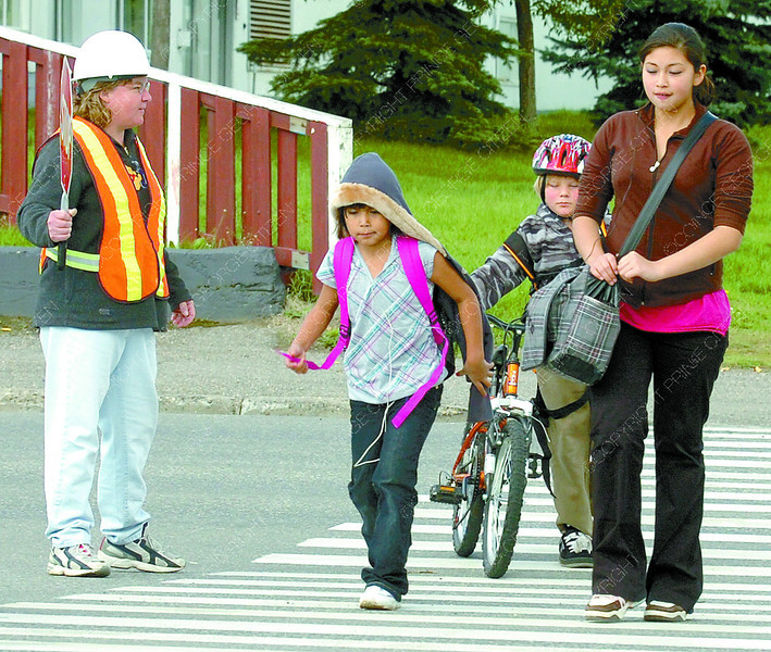 Citizen photo by David Mah Crossing guard Jill Marchant, stops traffic at 15th Avenue and Irwin Street so Zariah Clayton, 9, Noah Martinson, 9, and Nikeisha Clayton, 12, cross safely.